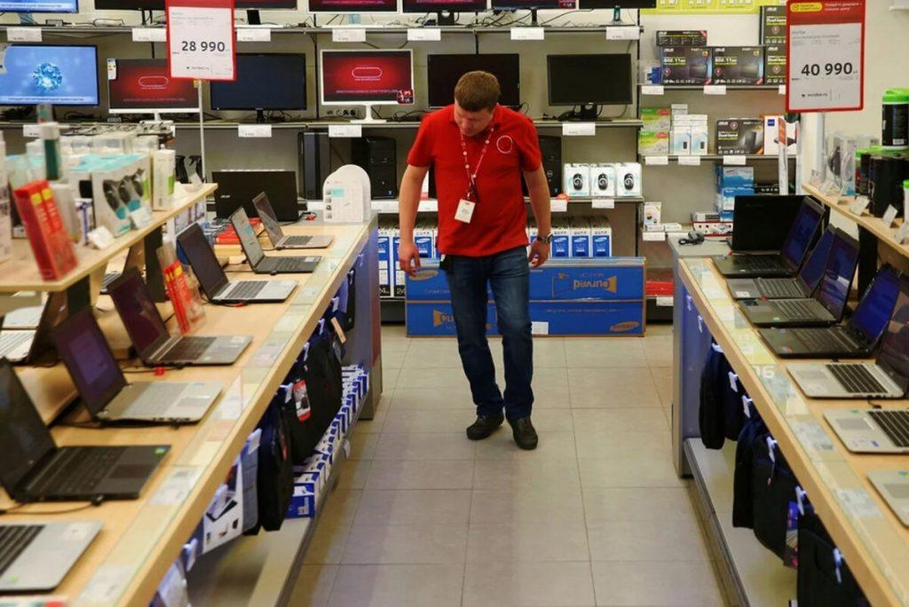 Выбирает ноутбук в магазине